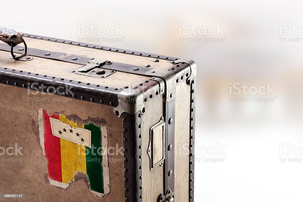 Old leather suitcase with flag of Guinea stock photo