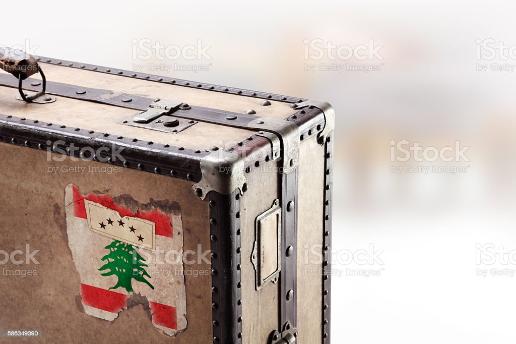 Old leather suitcase with flag of Lebanon stock photo