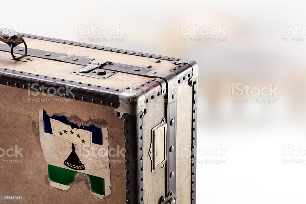Old leather suitcase with flag of Lesotho stock photo