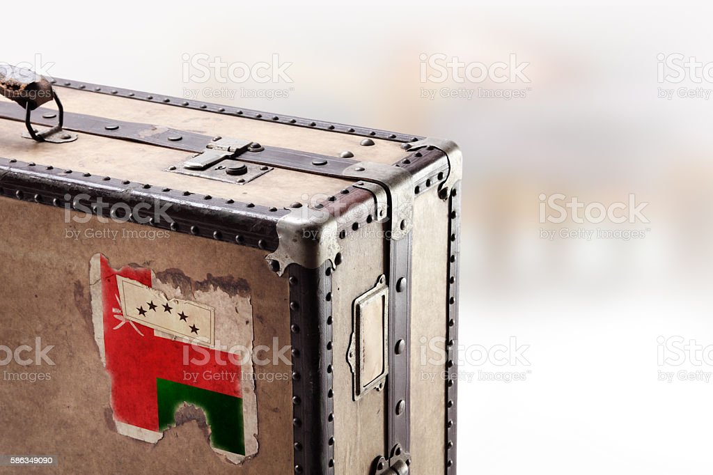Old leather suitcase with flag of Oman stock photo