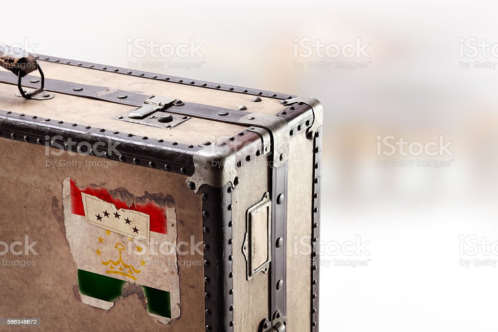 Old leather suitcase with flag of Tajikistan stock photo