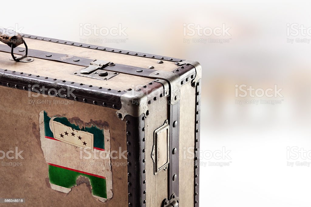 Old leather suitcase with flag of Uzbekistan stock photo