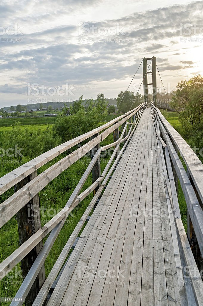 Old lengthy hanging wooden footbridge with rails against sunset background royalty-free stock photo