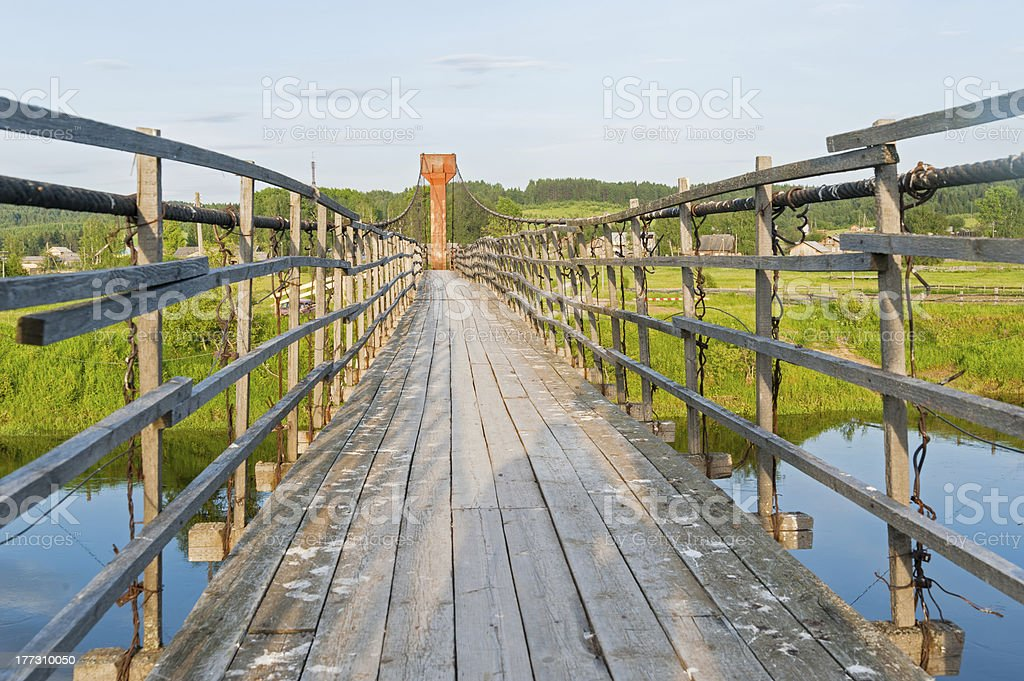 Old lengthy hanging wooden footbridge with rails over river royalty-free stock photo