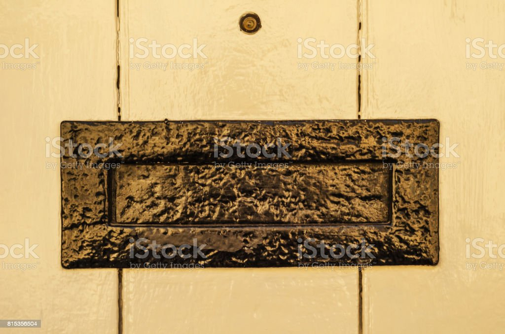 Old letterbox in the door, traditional way of delivering letters to the house, old mailbox stock photo
