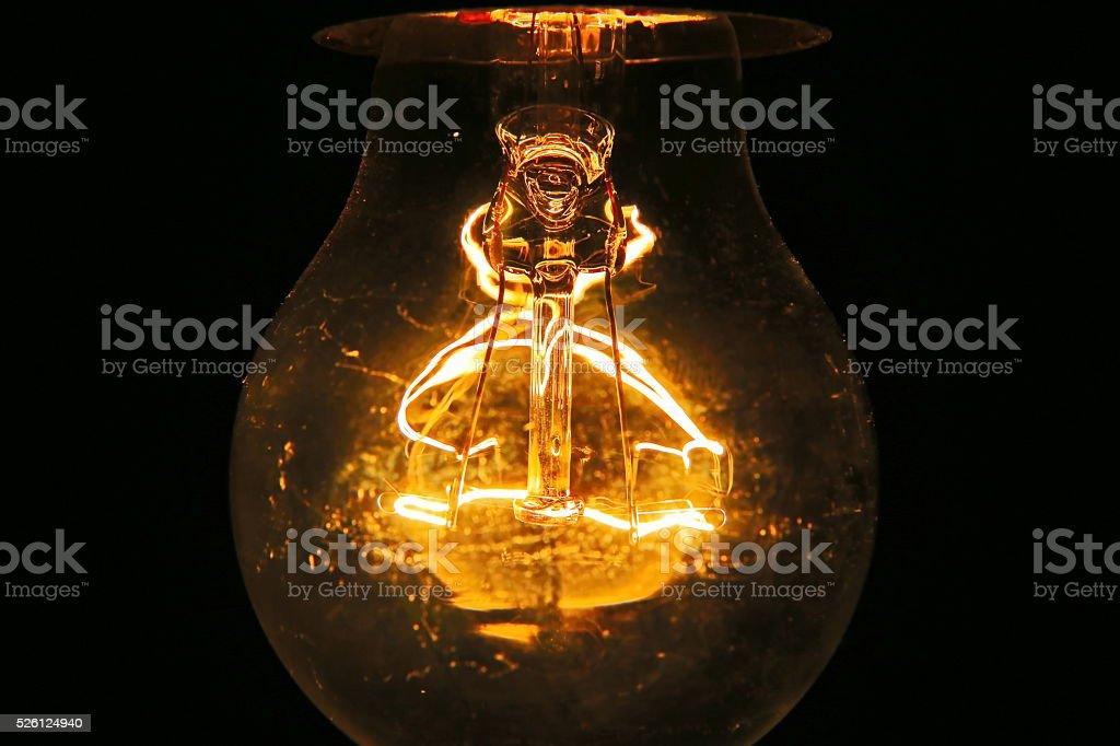 Old light bulb glowing in dark stock photo