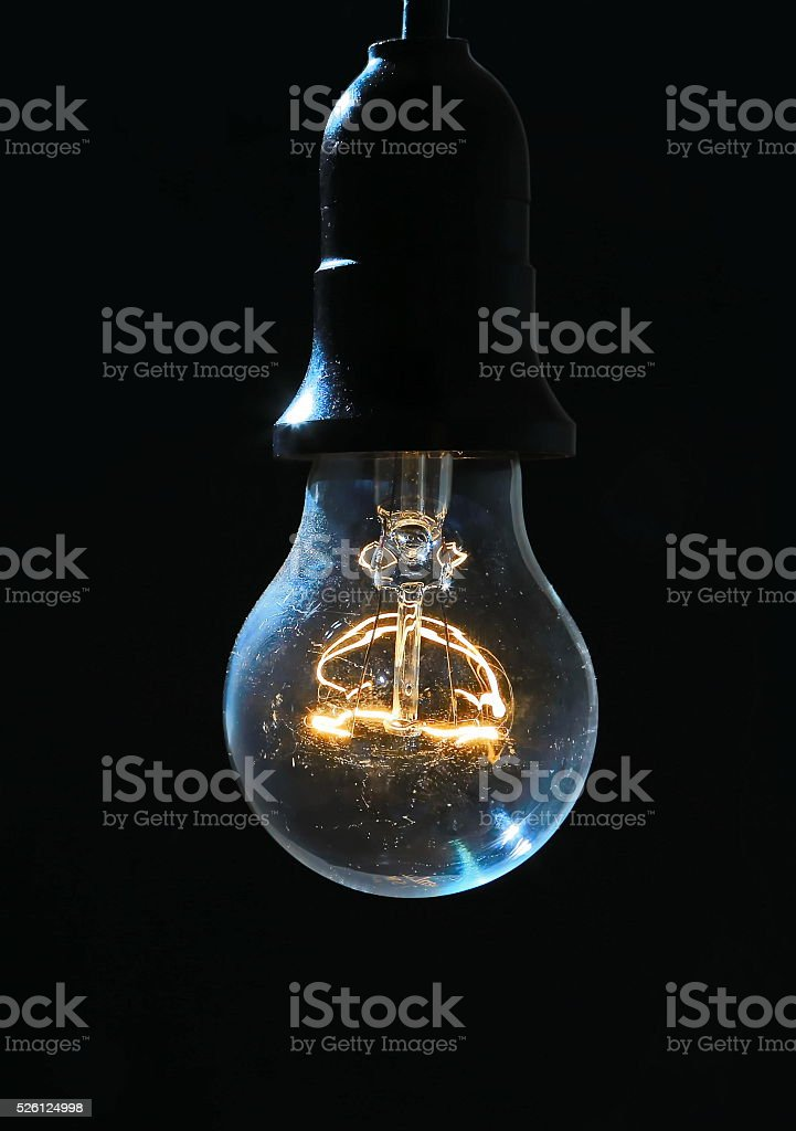 Old light bulb glowing in dark stock photo