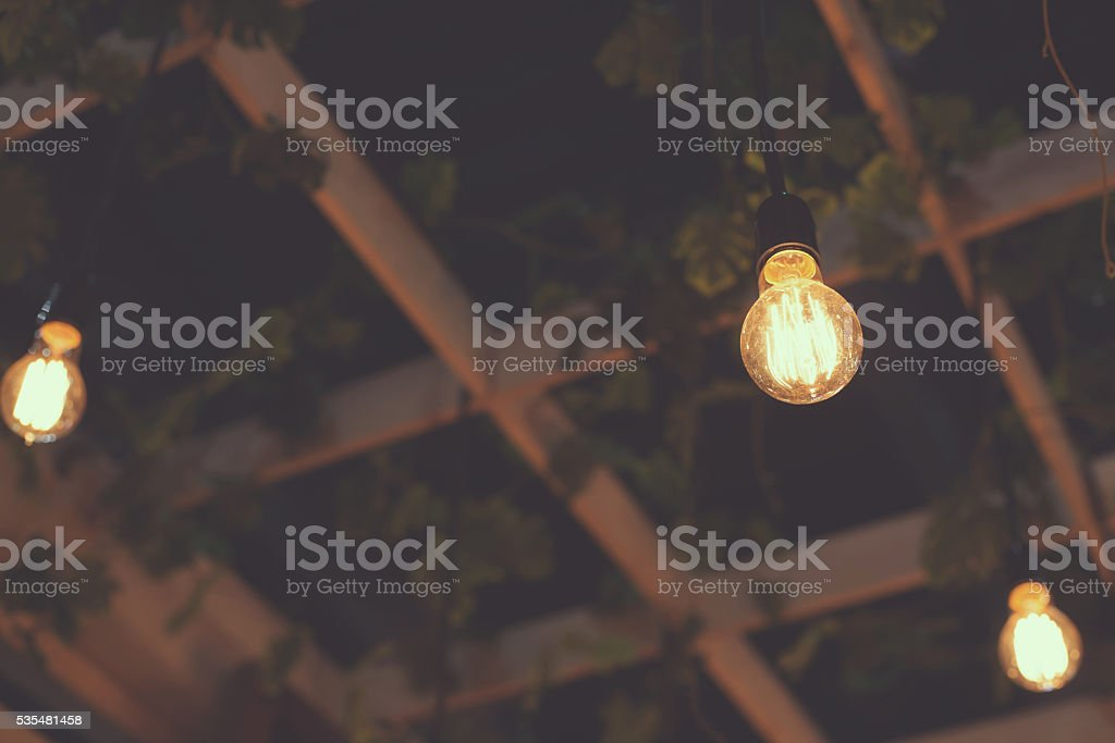 Old light bulb glowing in the dark. stock photo