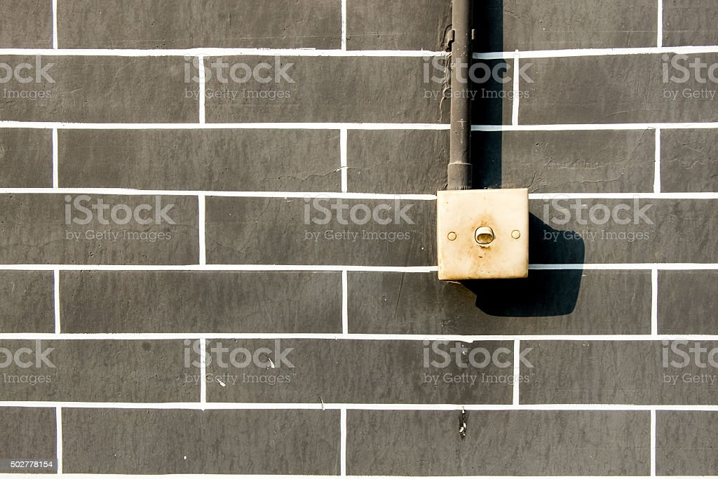 Old light switch on grey brick wall , outddor stock photo
