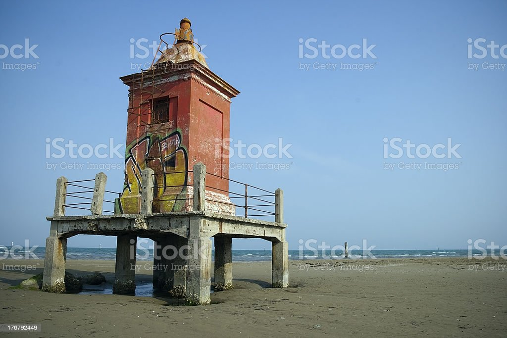 Old Lighthouse with Graffiti on the Beach Against Blue Sky royalty-free stock photo