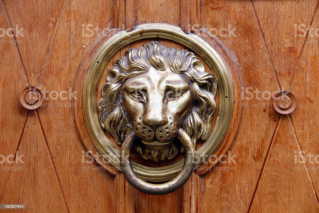 Old lion-head knocher on the wooden door stock photo