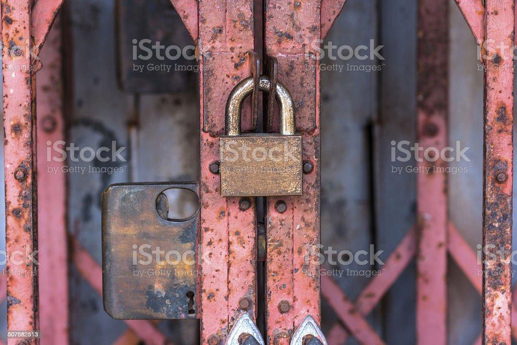 Old locked Padlock on the red door stock photo