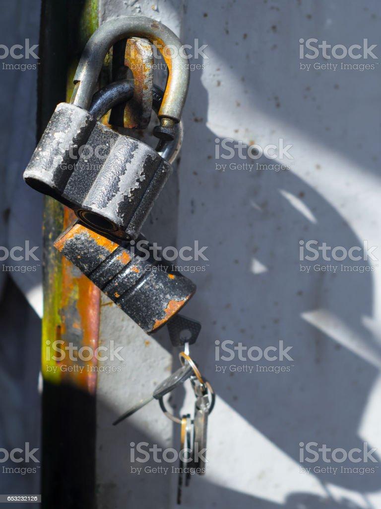 Old locks with keys on garage door stock photo