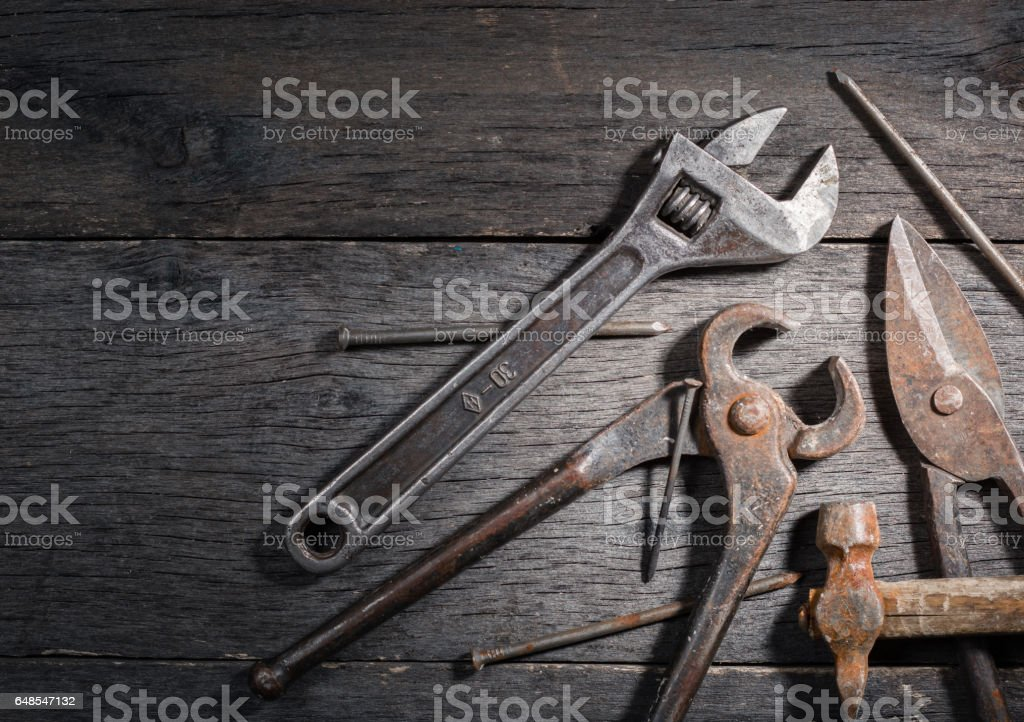 Old locksmith tools on a gray and cracked wooden background. stock photo