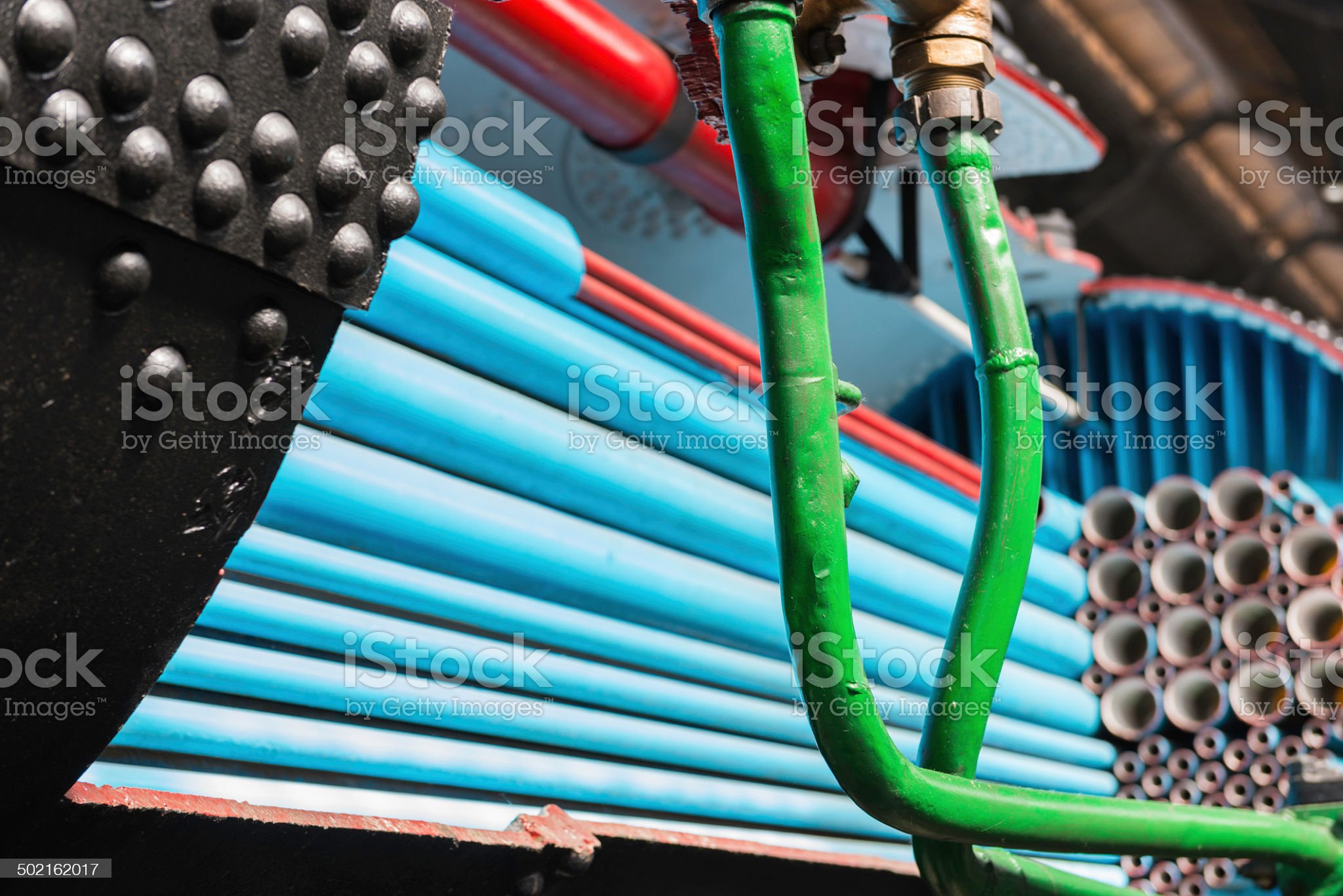 Old locomotive boiler painted in blue, green and red royalty-free stock photo