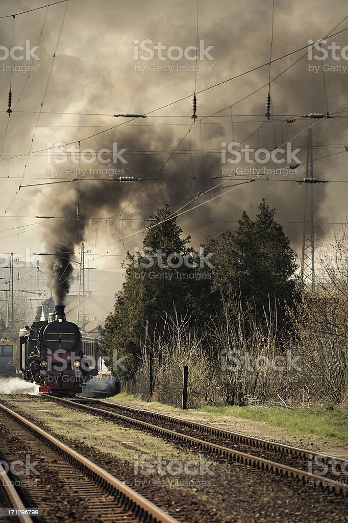 old locomotive leaving the railway station stock photo