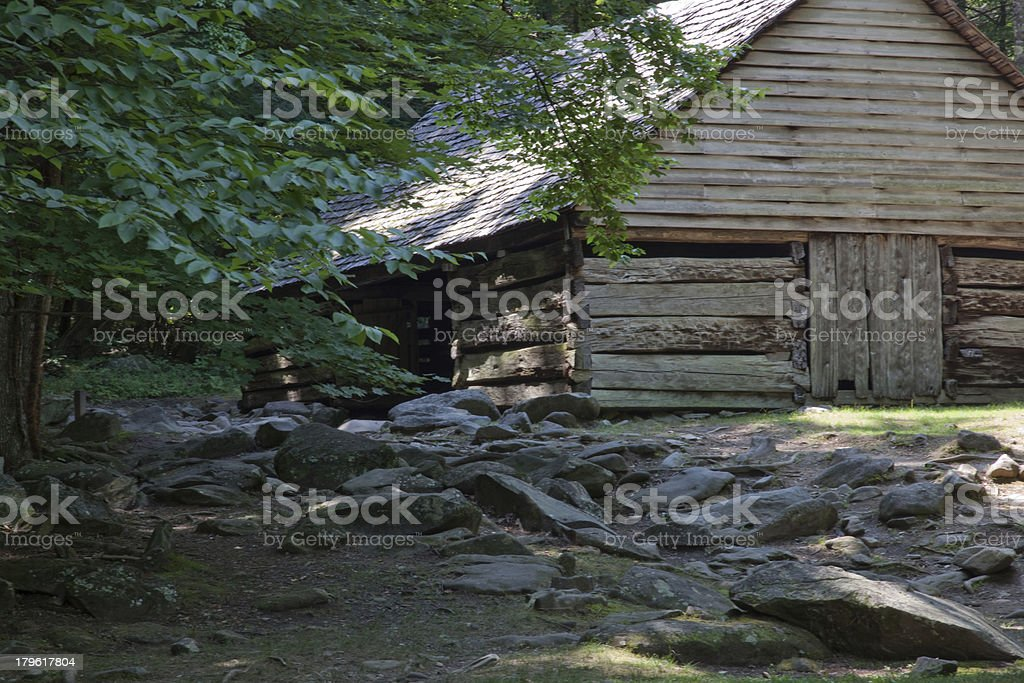 Old log barn, surrounded by trees royalty-free stock photo