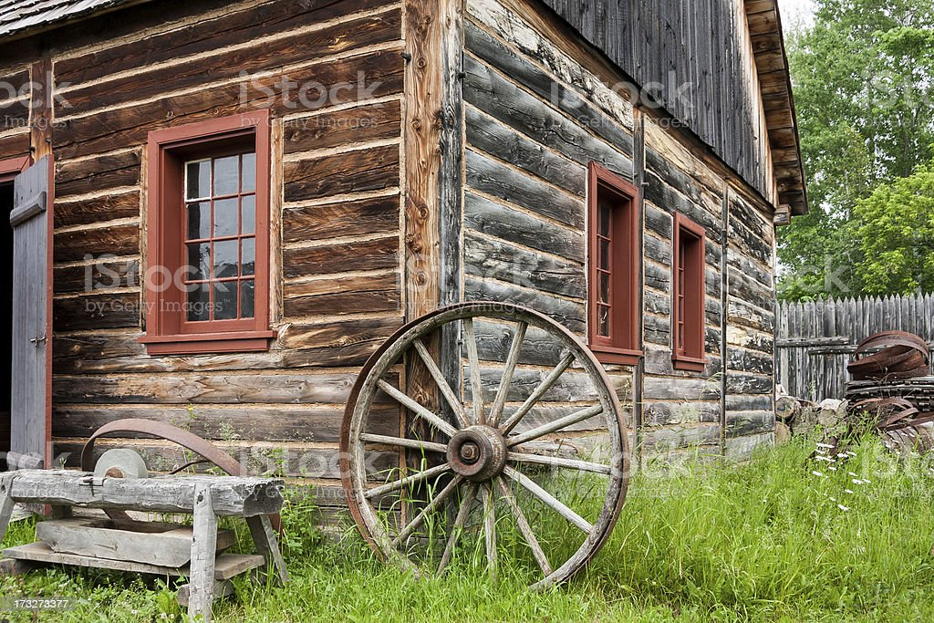 Old log house with wooden spoke wheel against the wall. royalty-free stock photo