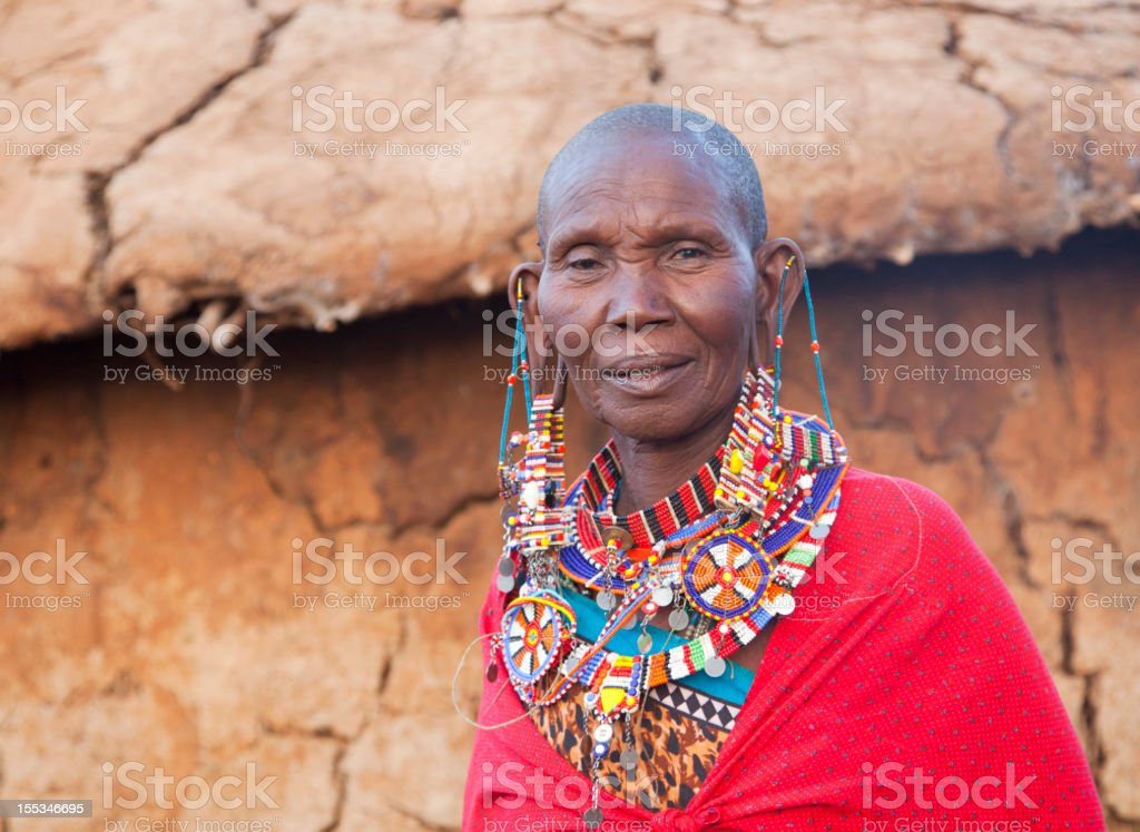 Old maasai woman with traditional jewellery in front of hut stock photo