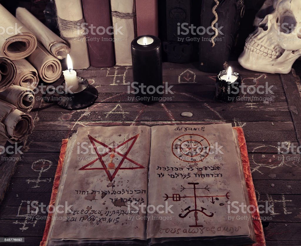 Old magic book and black candles on witch table stock photo