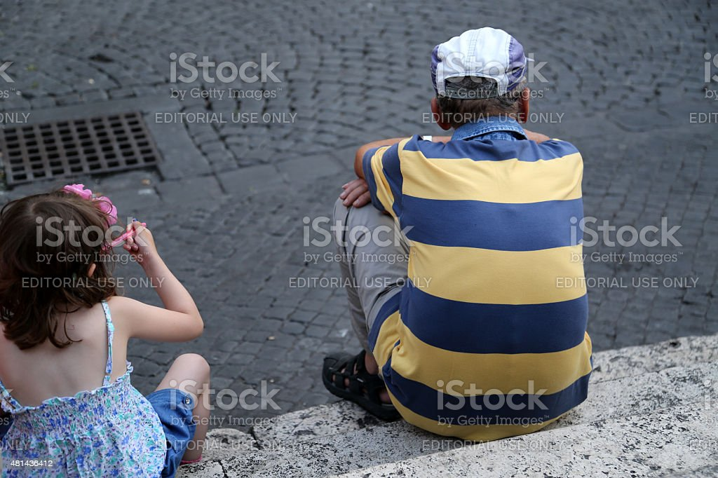 Old man and child sitting on stairs in Trastevere. stock photo