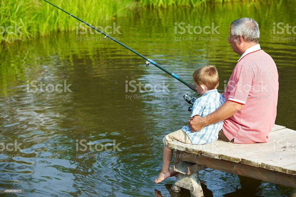 Old man and little boy fishing at a lake stock photo