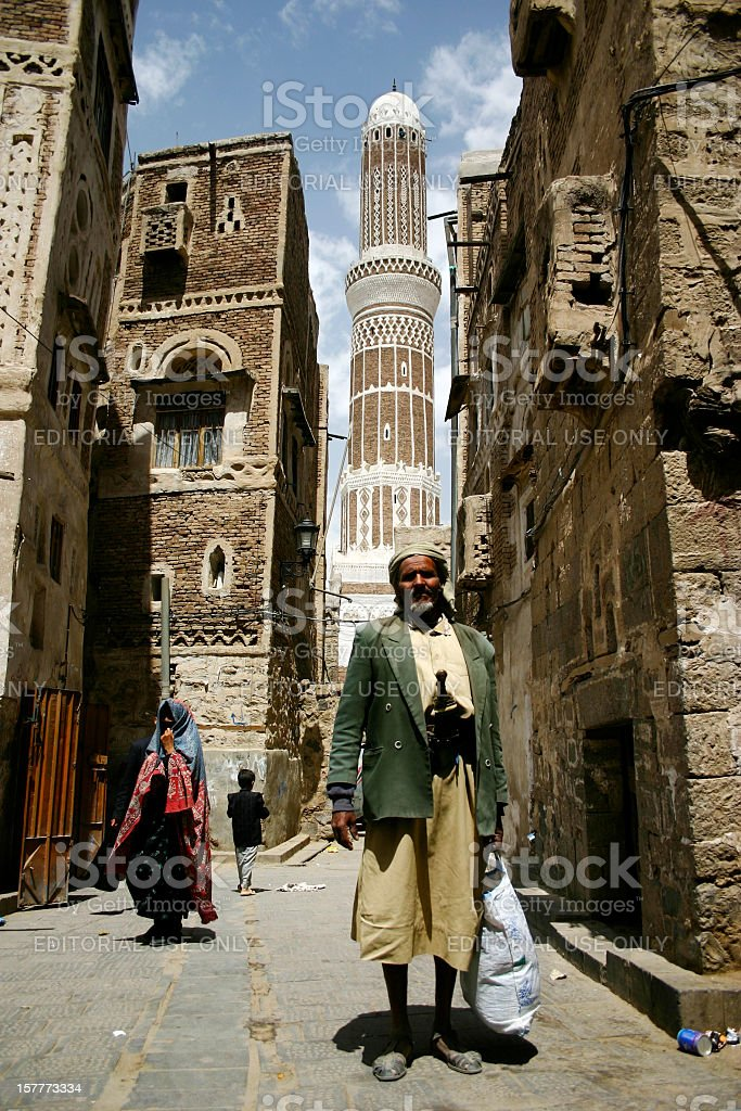 Old man and minaret stock photo