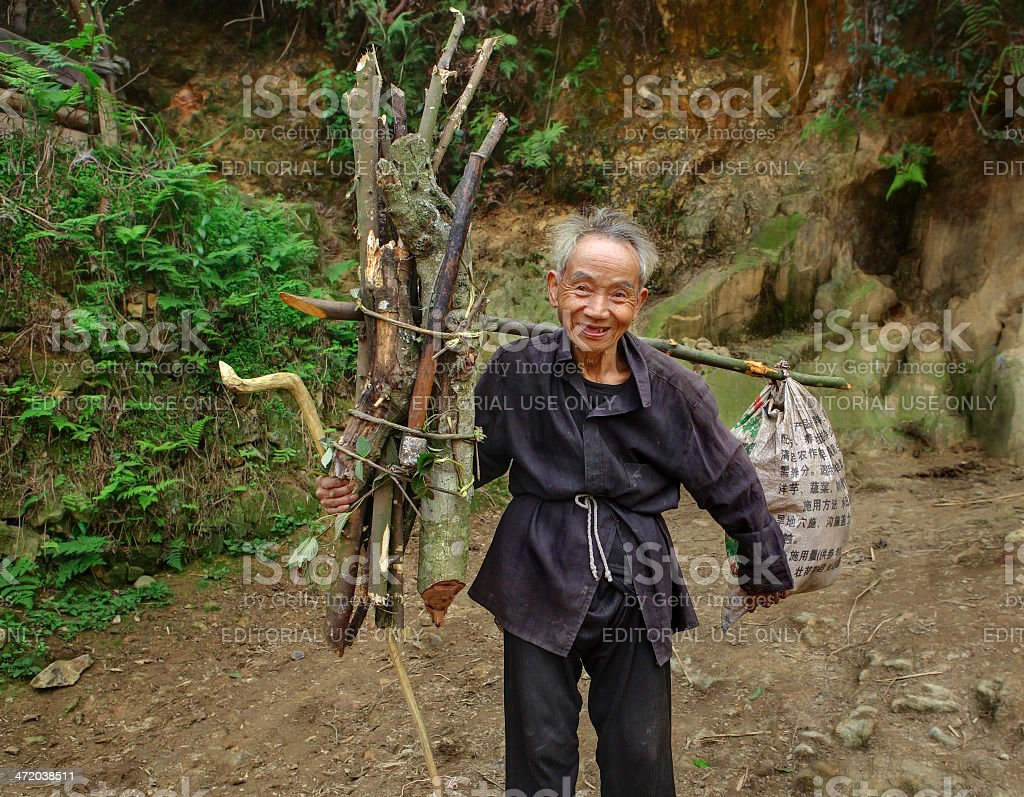 Old Man Asian, with bunch fagots, goes on mountain trail. stock photo