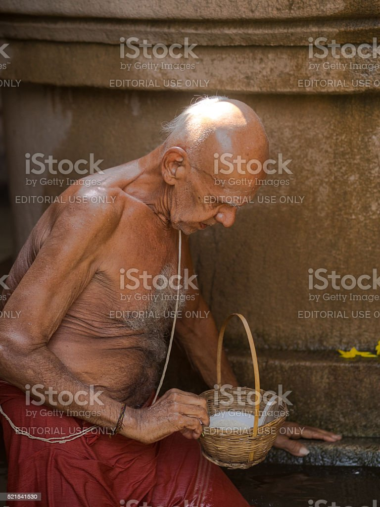 Old man at a temple in Hampi, Southern India stock photo