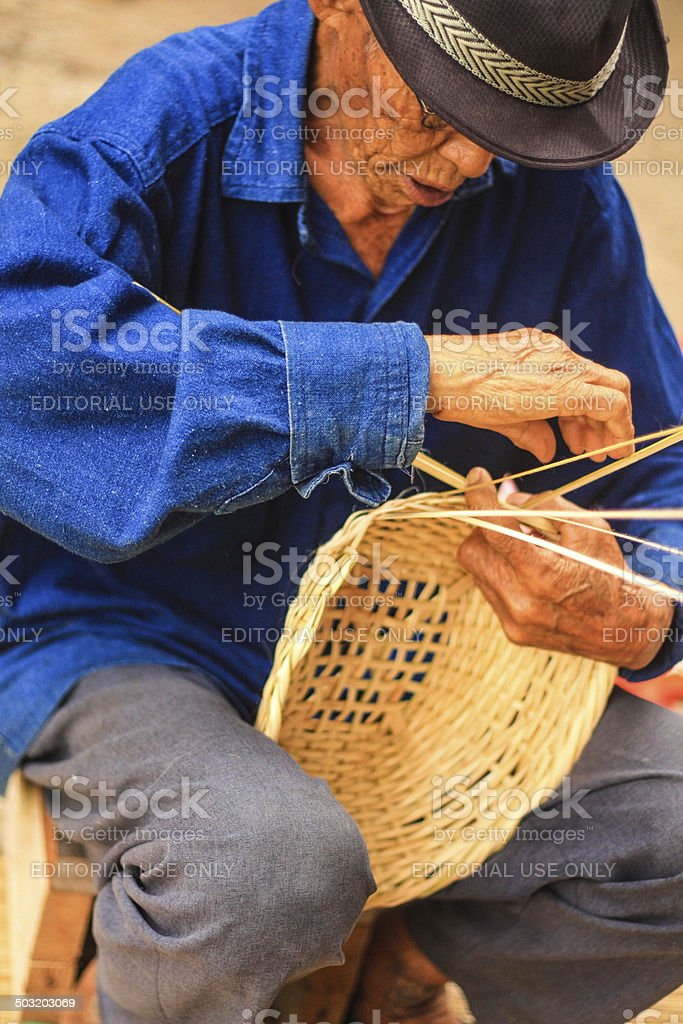 Old man Basket weaving from bamboo stock photo