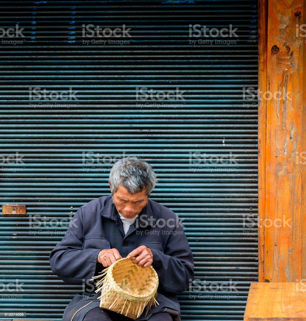 Old man Basket weaving from bamboo, village Zhao Xing. stock photo