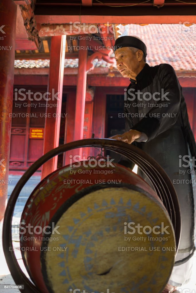 Hanoi, Vietnam - July 24, 2016: Old man beating drum made of wood and water buffalo leather at Temple of Literature (Van Mieu), Hanoi. The man wearing Vietnamese old traditional long dress Ao Dai stock photo