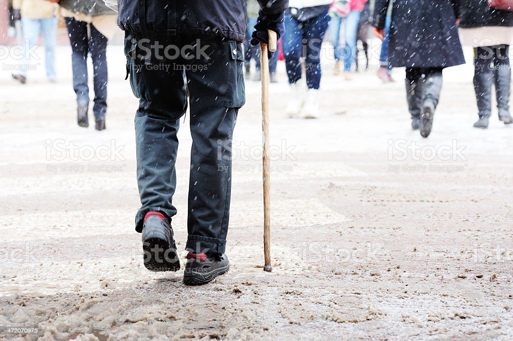 Old man crossing slippery snow covered street stock photo