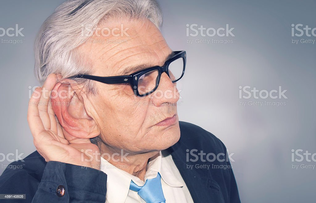 Old man cupping his ear to hear something stock photo