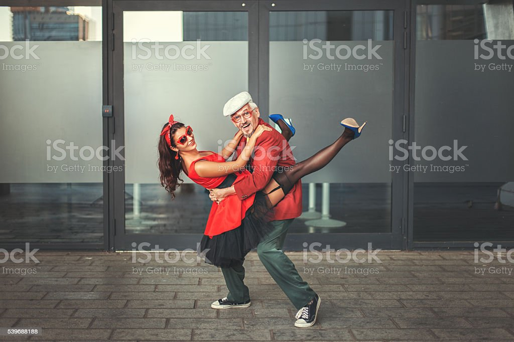 Old man dancing with a young woman fast dance.