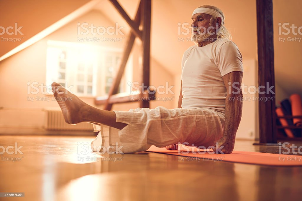 Old man doing balance exercises in a health club. stock photo