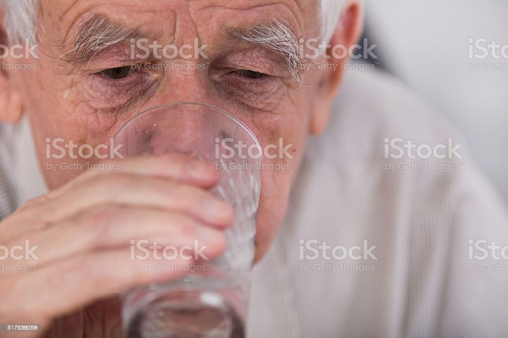 Old man drinking water stock photo