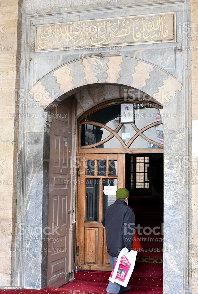 Old man entering historical mosque stock photo
