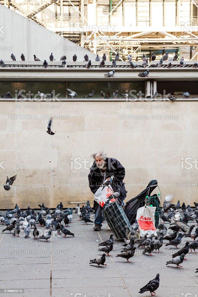 Old man feeding pigeons near the Pompidou Center, Paris, France stock photo