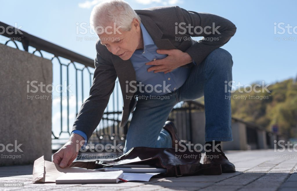 Old man finding unexpected envelope in his bad in the street stock photo