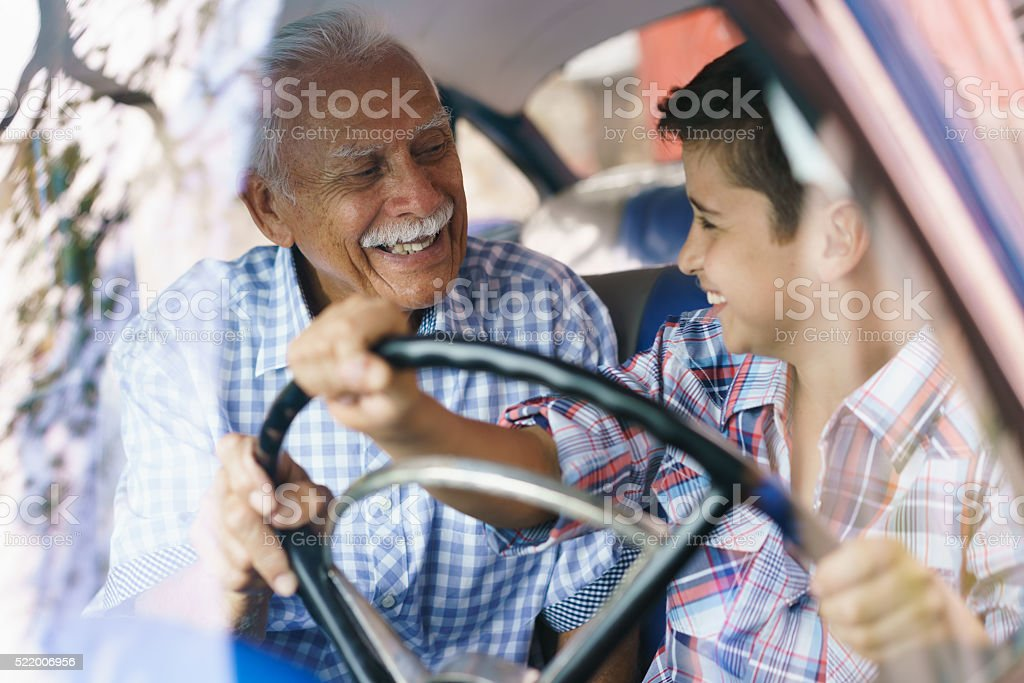 Old Man Grandpa Gives Driving Class To Grandson stock photo