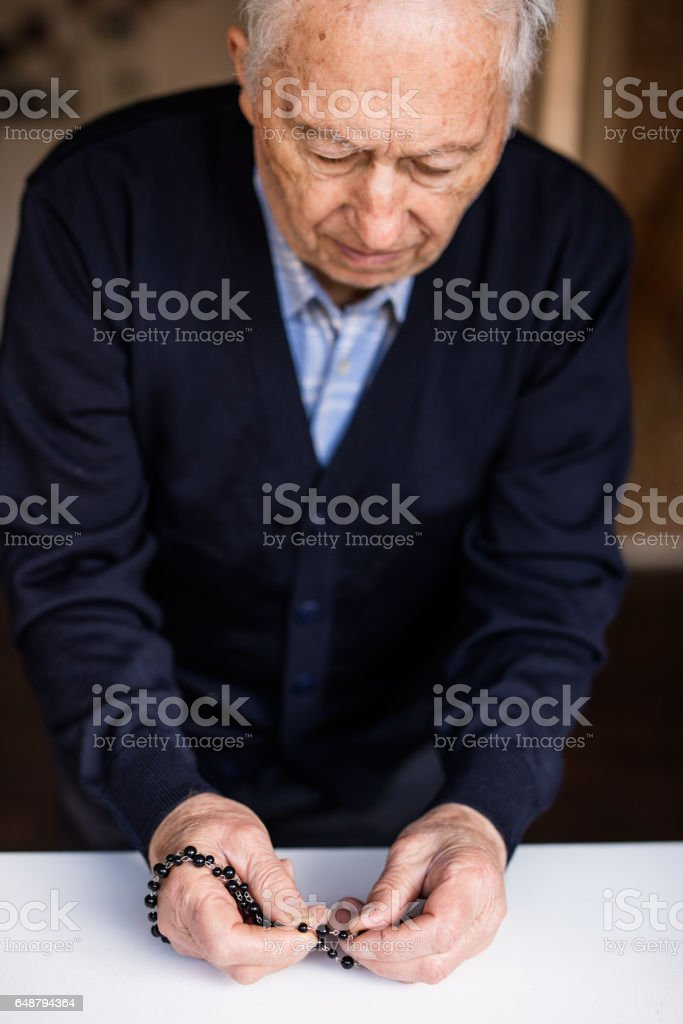 Old man hands with classic rosary stock photo