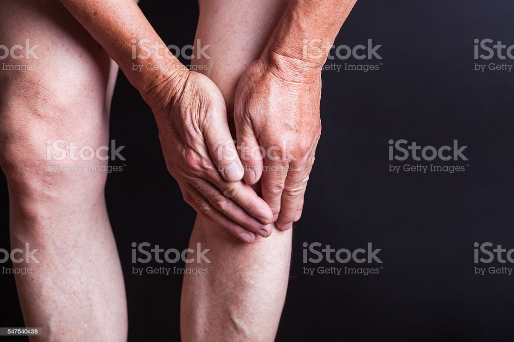 old man holding his knees with black background stock photo