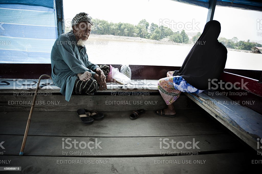 Old man in traditional wooden river boat. stock photo
