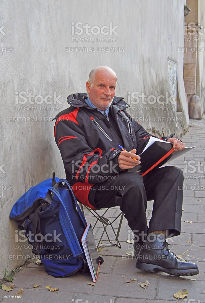 old man is drawing something outdoor in Krakow, Poland stock photo
