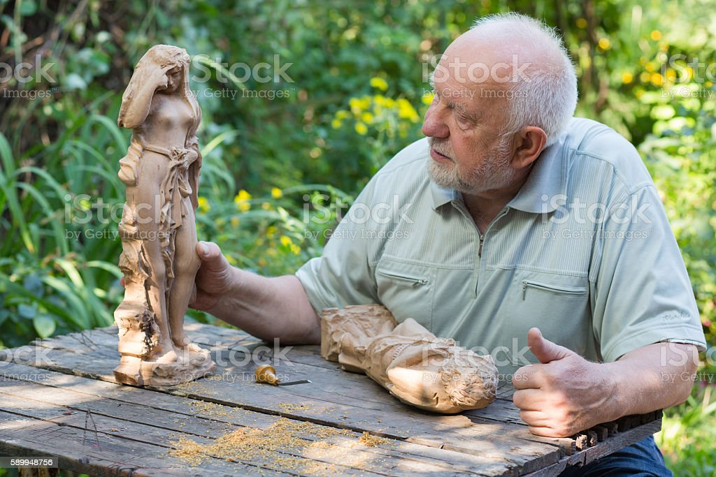 Old man is keen on woodcarving stock photo