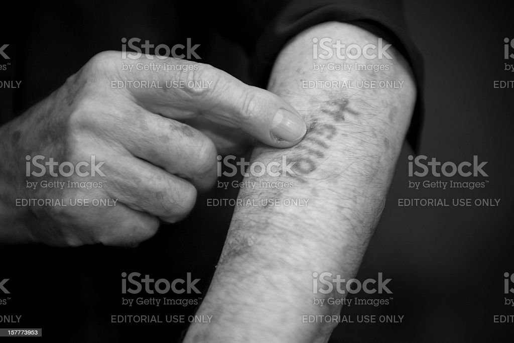 Old man is showing his number he got in Ausschwitz stock photo