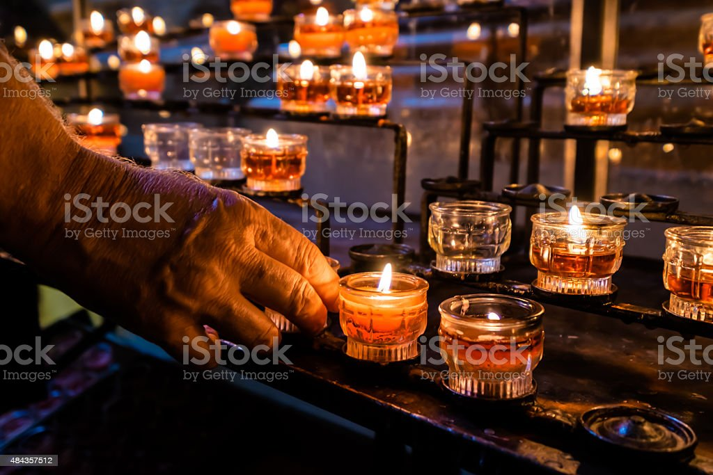 Old Man lighting a candle in a church stock photo