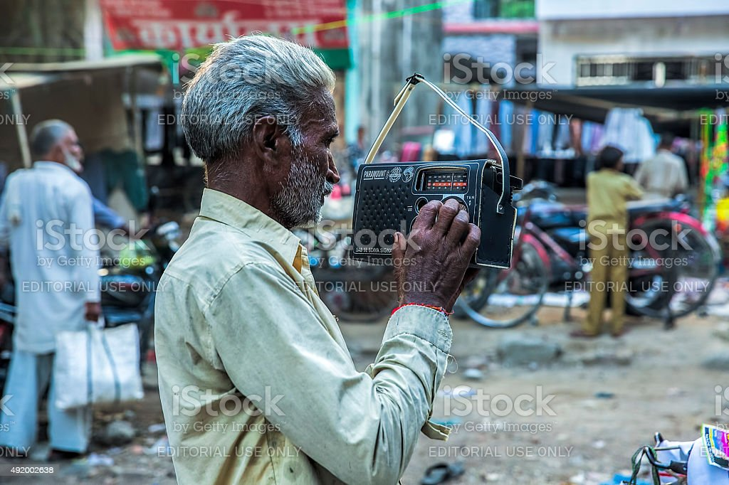 Old man listening to an old fashioned Radio set stock photo