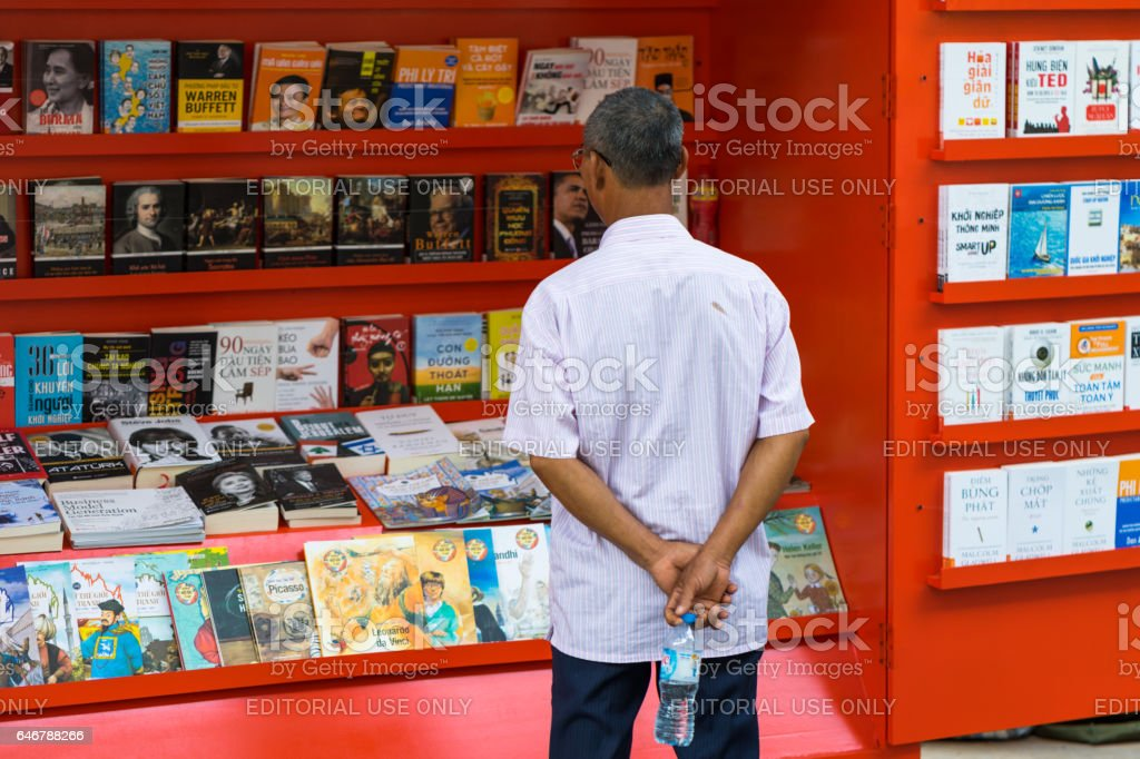 Hanoi, Vietnam - Sep 2, 2016: Old man looking at book stall on Le Thach street stock photo